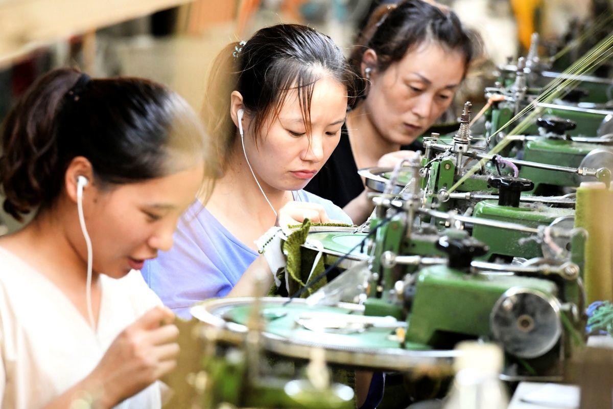 8月14日中國公佈的重要經濟數據顯示,由於零售銷售放緩,投資今年前七個月跌至創紀錄低位。圖為2018年8月13日,中國河南省商丘市夏邑縣一家工廠生產出口服裝的員工在生產線上。(STR/AFP/Getty Images)