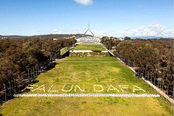 2014年9月27日,三百多名法輪功學員在澳洲坎培拉國會大廈前排字。(Henry Lam/大紀元)