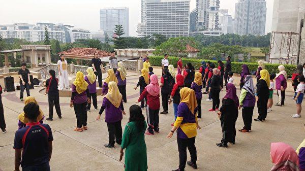 主辦方安排了法輪功學員在柔佛州新山伊斯干達(Kota Iskandar, Johor Bahru)州政府辦公樓前教功,上百名與會者當場學煉法輪功。(明慧網)