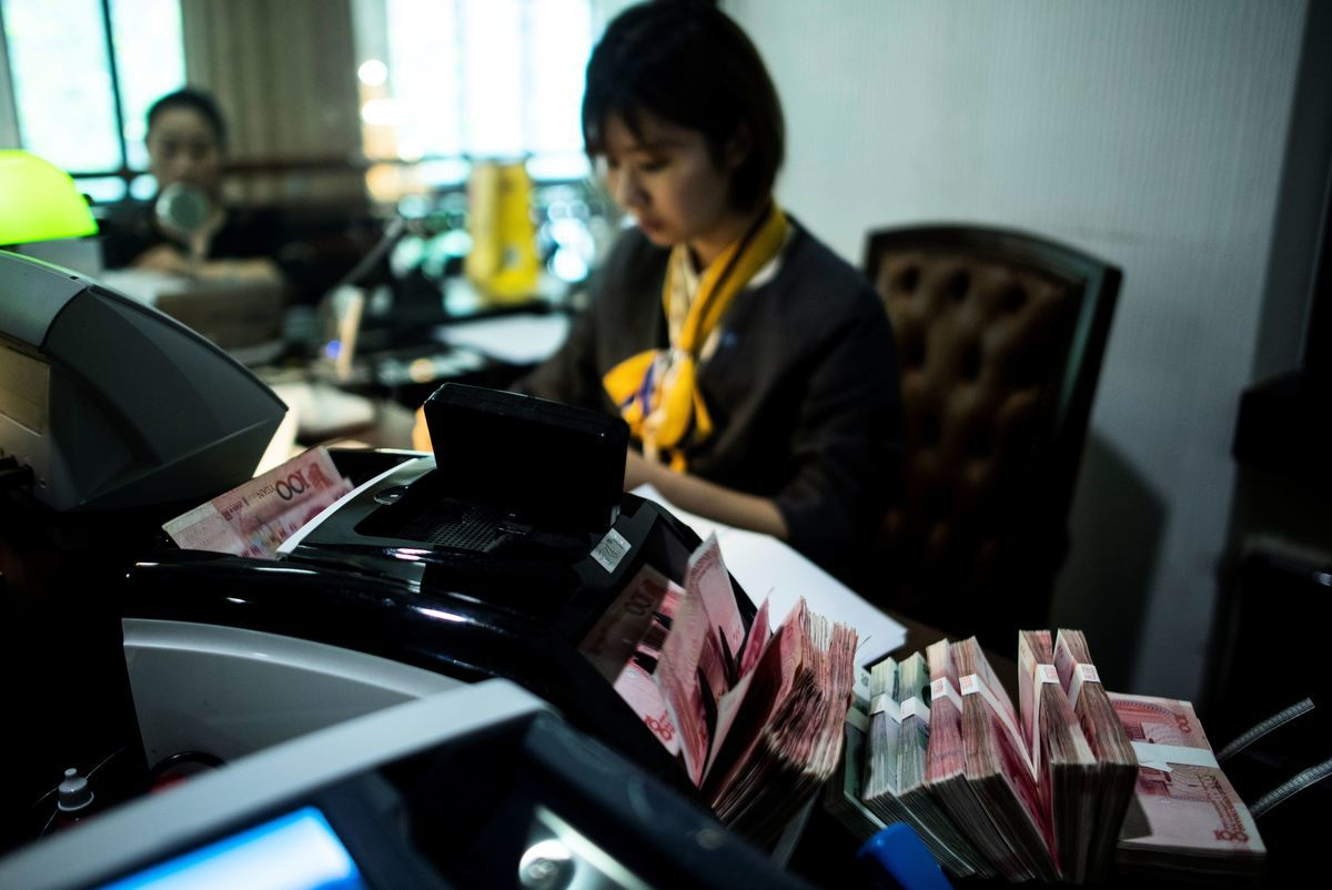 CNBC報道說,中國經濟原本存在很多問題,在美中貿易戰的影響下,中國經濟將受到衝擊。圖為2018年8月8日,上海一家銀行的職員在清點人民幣鈔票。(JOHANNES EISELE/AFP/Getty Images)