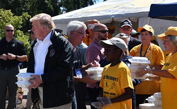 特朗普總統在災區為民眾發放食品。(NICHOLAS KAMM/AFP/Getty Images)