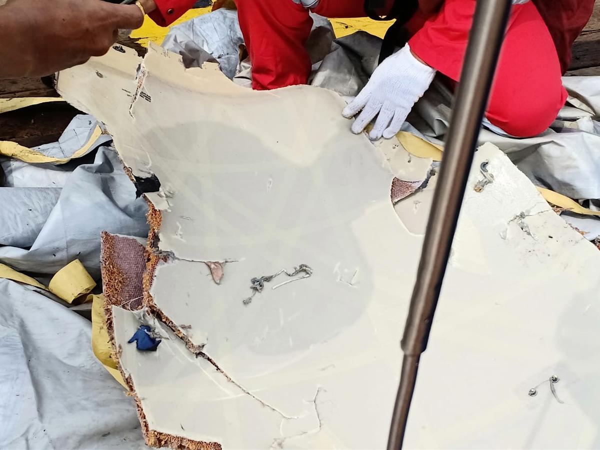 相關人員在查看疑似失事飛機的殘骸碎片。(Handout/various sources/AFP)