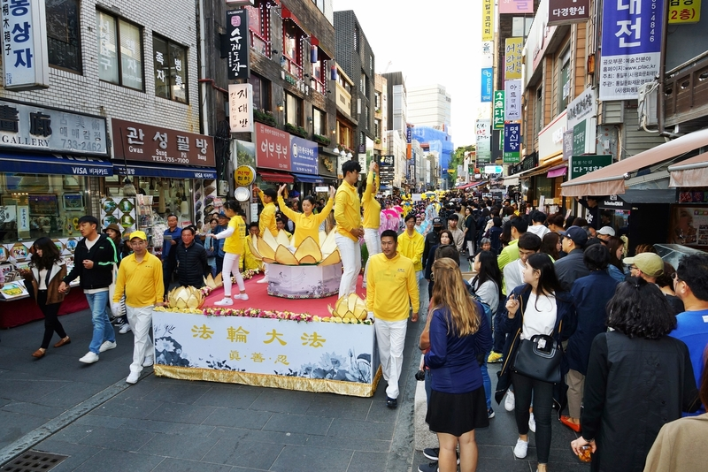2018年10月13日,南韓首爾,來自亞洲十多個國家的法輪功學員在首爾市中心舉行反迫害大遊行。圖為花車上的法輪功學員在煉功。(全景林/大紀元)