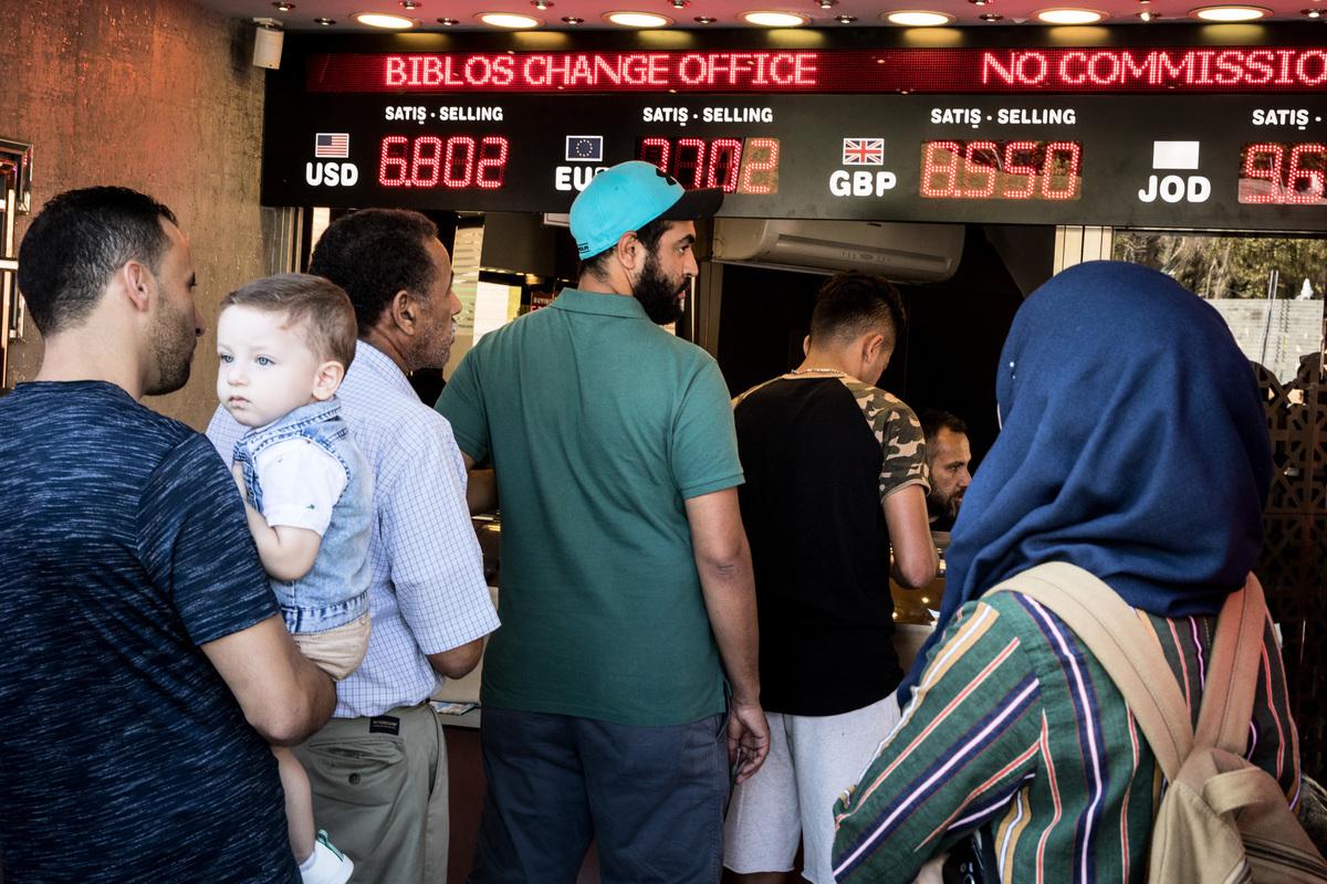 2018年8月13日,因土耳其里拉匯率受美國制裁影響重挫,土國民眾在銀行排隊搶兌外匯。(Chris McGrath/Getty Images)