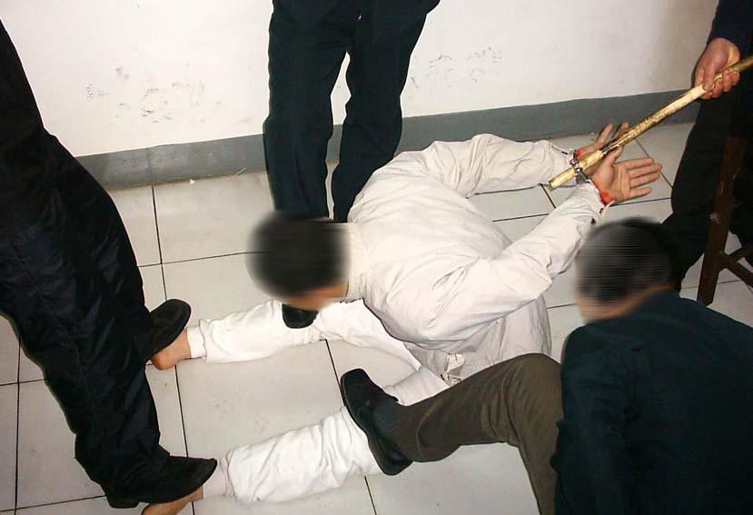 中共酷刑示意圖:手銬別木棒。(明慧網)
