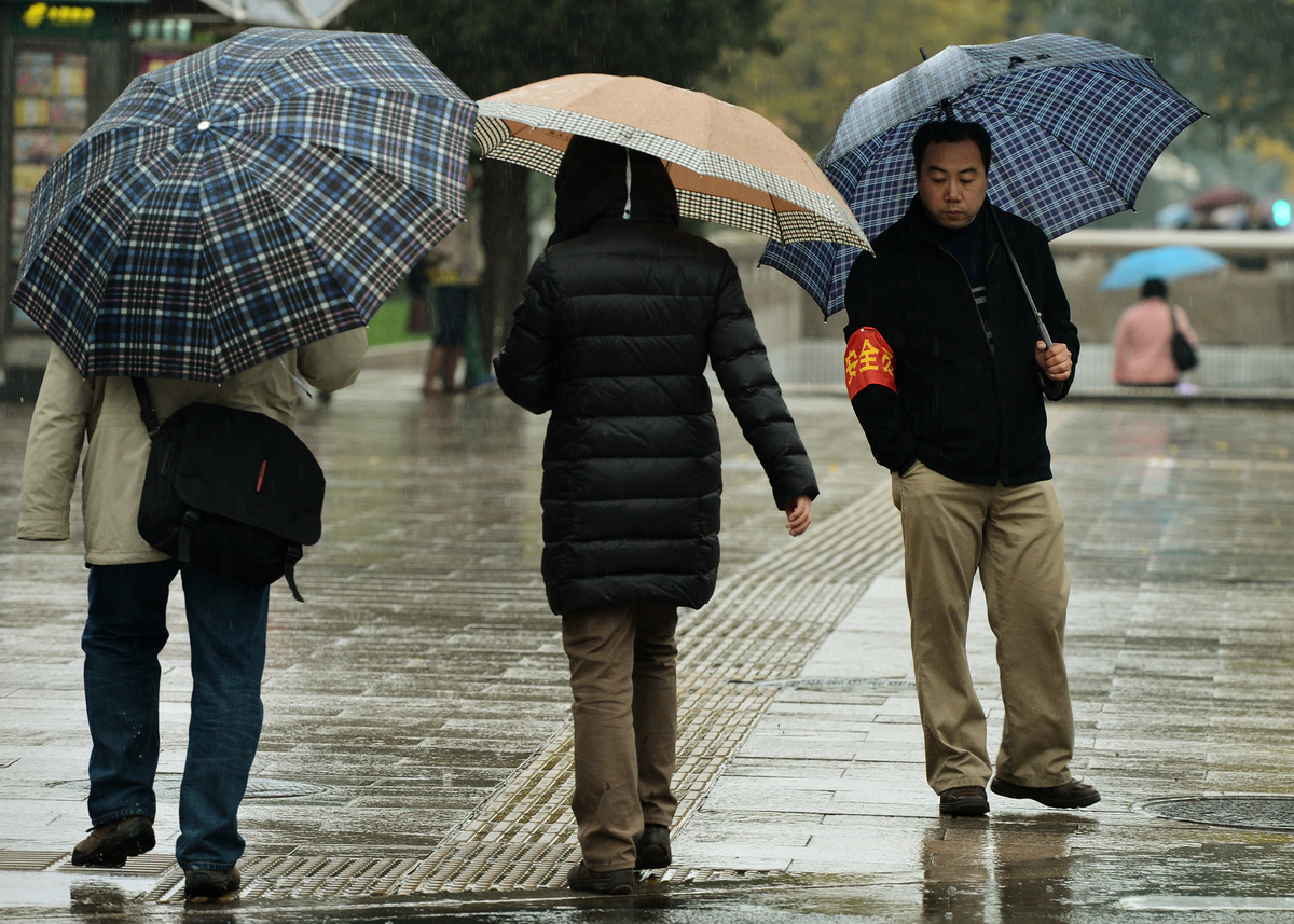 有評論指,中共最大的恐懼擔憂就是社會不穩定以及讓其放鬆對中國政治體制的嚴格控制,但它卻不知道真正的威脅會在何時、何處出現。圖為北京街頭戴紅袖章的社會維穩人員在人民大會堂附近監控過往行人的一舉一動。(MARK RALSTON/AFP/Getty Images)