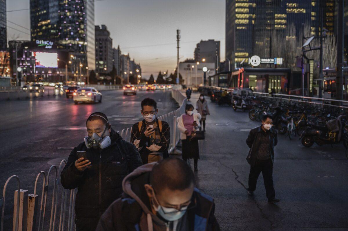 2020年3月20日,北京,中國上班族戴著防護口罩排隊等候巴士。(Kevin Frayer/Getty Images)