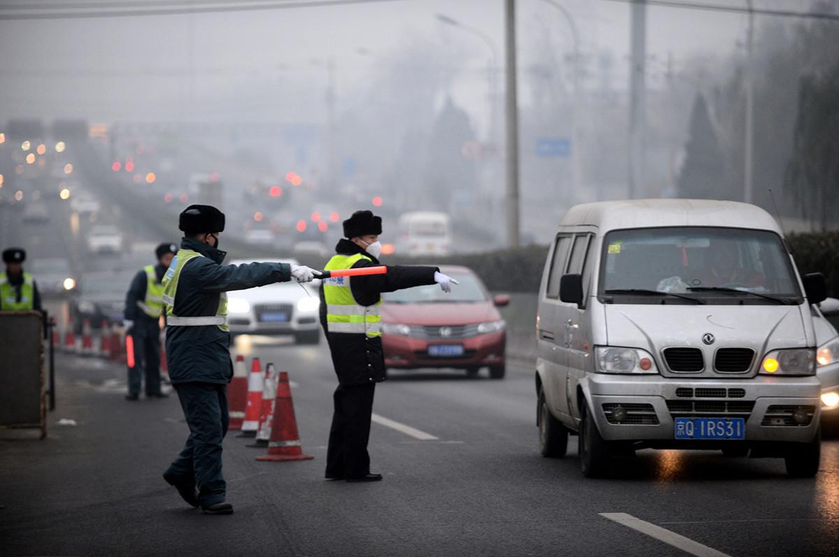 網上影片顯示,一名大陸男子在被警察臨檢時要求對方出示證件,以證明其身份。圖為2015年12月8日,北京馬路上的交通警察。(STR/AFP via Getty Images)