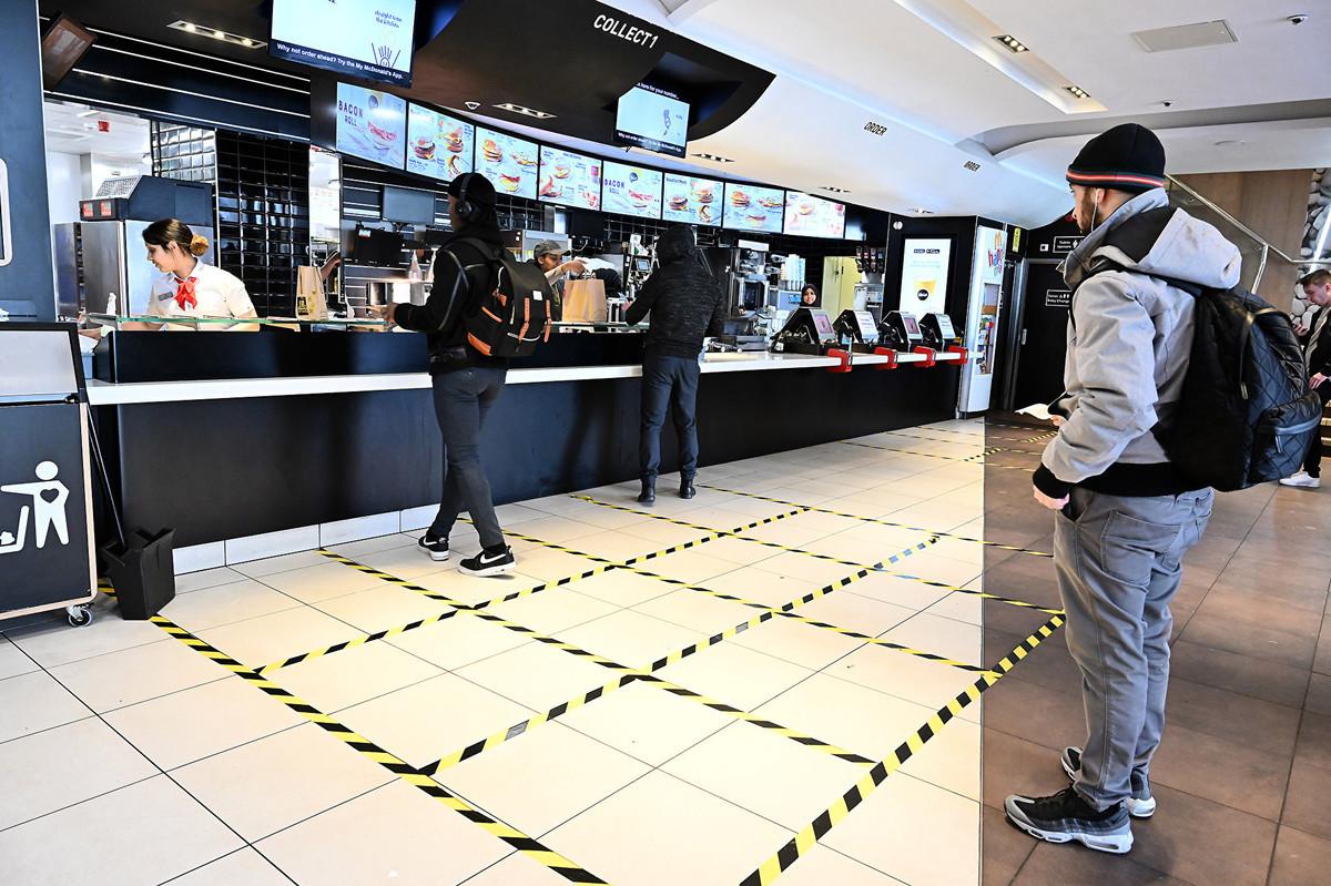 英國一家麥當勞店裏「保持社交距離」的顧客。(JUSTIN TALLIS/AFP)