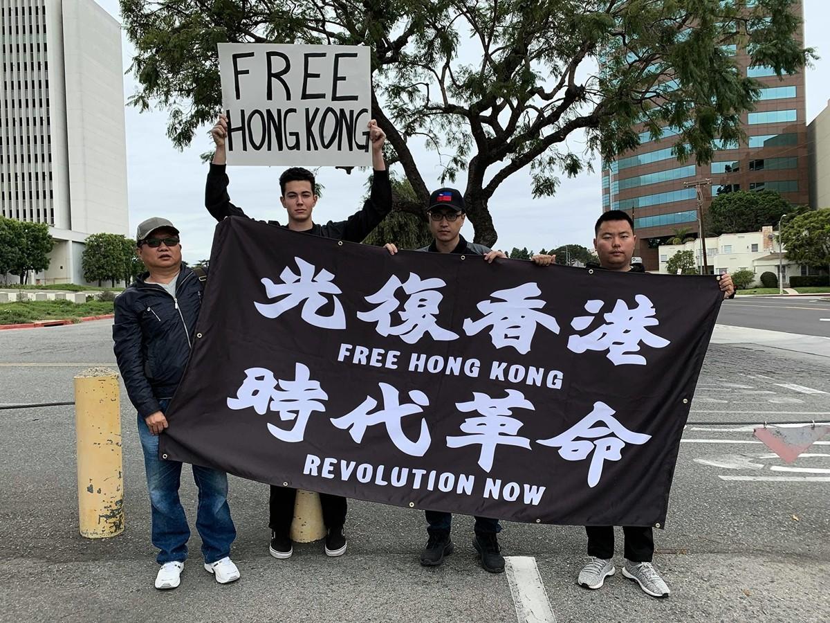 活動開始前,18歲的克萊因(左二)接受採訪時表示,中共不僅威脅著中國大陸、香港民眾的自由,更企圖操控全世界。(姜琳達/大紀元)