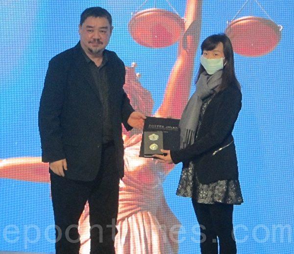 台灣立法院人權促進會副秘書長吾爾開希(左)為獲得銀獎的日本學生大橋輪頒獎,圖右女士為代領獎者。(鍾元/大紀元)