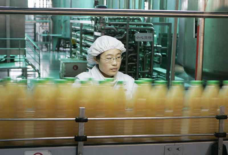 一位女工在匯源果汁廠流水線上工作。(Getty Image)