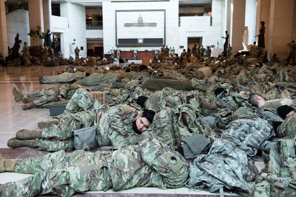 2021年1月13日,國民警衛隊成員躺在華盛頓國會山的國會遊客中心休息。 (SAUL LOEB/AFP via Getty Images)