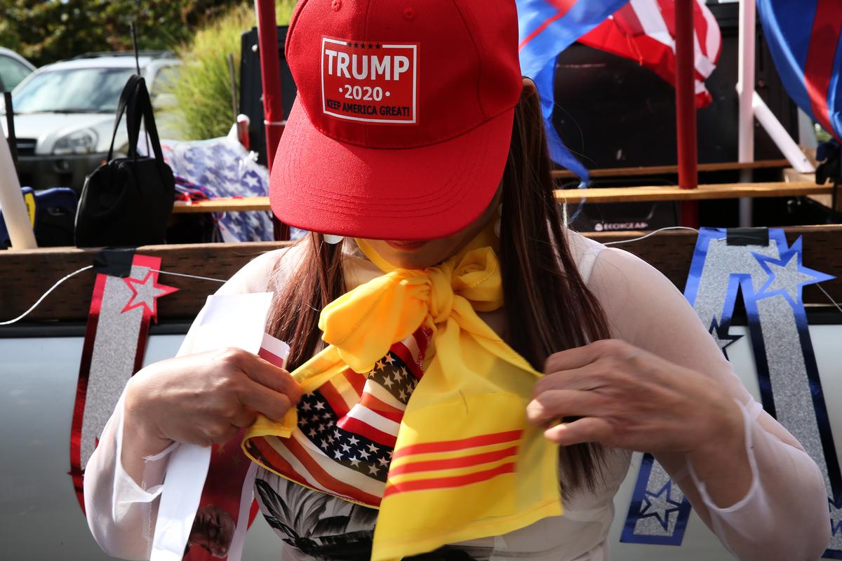 來自越南的Holly Tran於2020年10月10日在華盛頓的埃弗里特(Everett)參加支持特朗普的活動。圖為Tran正在整理印有美國和越南國旗色的絲巾。(Karen Ducey/Getty Images)