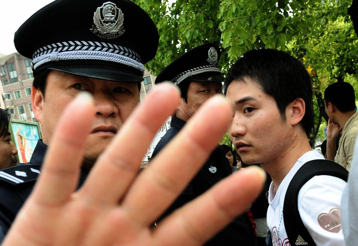 中共警察扣留學生,阻止外國記者拍照。(MARK RALSTON/AFP/Getty Images)