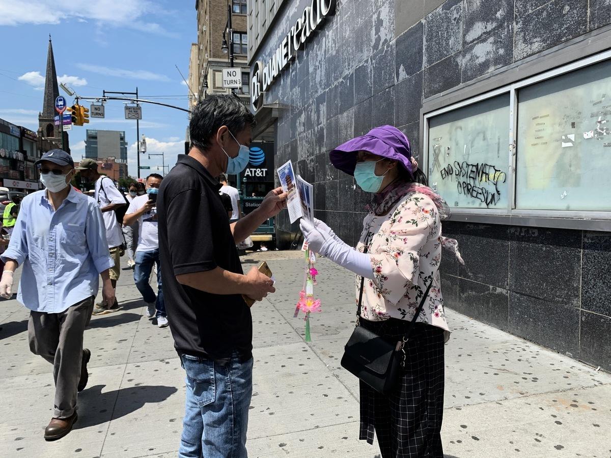華人民眾路過紐約華人社區法拉盛的真相點,接過「法輪大法好」的資料。(林丹/大紀元)