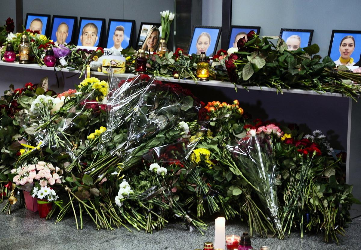 在2020年1月8日,烏克蘭航空空難中不幸遇難的空乘人員照片前擺滿鮮花和蠟燭。(加通社)