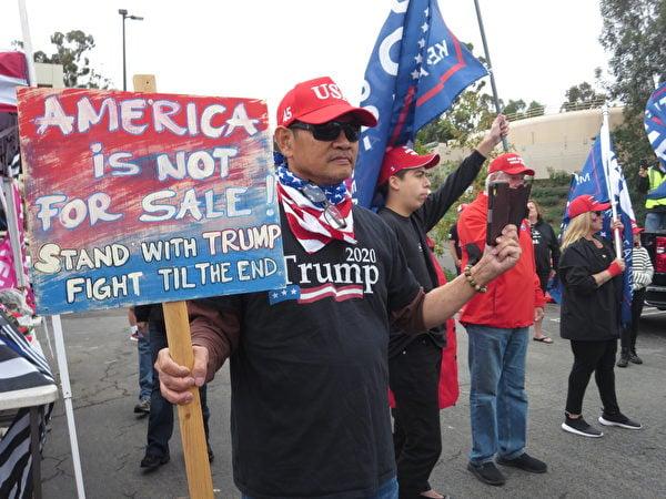 參加抗議選舉舞弊集會的民眾,牌子上寫著「美國不能被出賣,和特朗普總統站在一起,戰鬥到底(李梅/大紀元)
