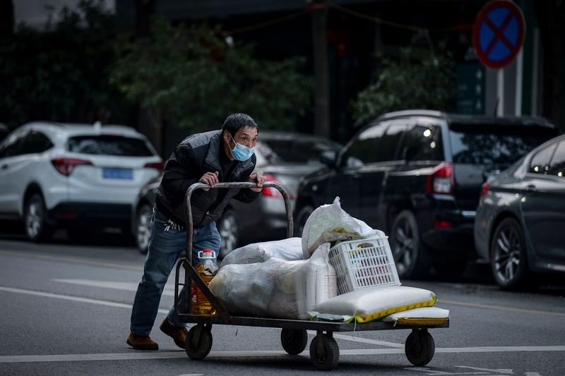 2020年3月3日,湖北省武漢市,推著食物推車的男子戴上口罩防護。(STR/AFP via Getty Images)