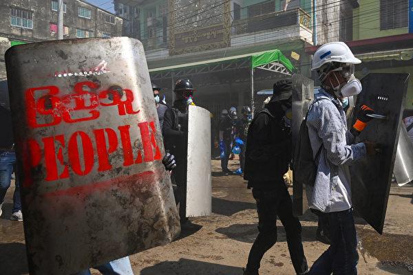 2021年3月8日,仰光民眾在街頭手持自製盾牌,來防禦武警的催淚彈。(STR/AFP via Getty Images)