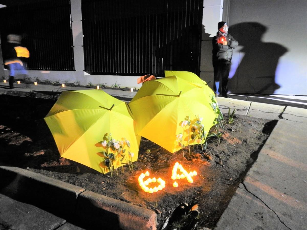 2021年6月4日晚,在阿德萊德東郊Joslin區中領館前的六四悼念集會現場,活動者用燃亮的燭光排成「6.4」字樣,擺出象徵香港民主運動的黃雨傘,並獻上對六四殉難者致悼的鮮花。(李倩西/大紀元)