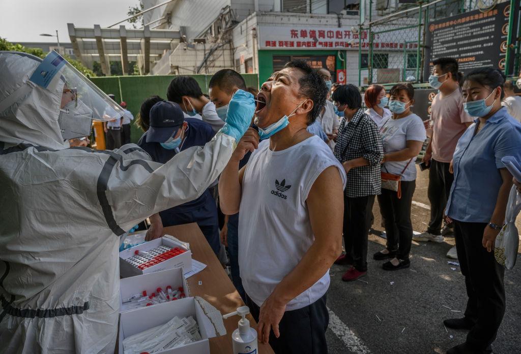 2020年6月16日,與新發地批發市場有過接觸的北京市民排隊接受核酸檢測。(Kevin Frayer/Getty Images)