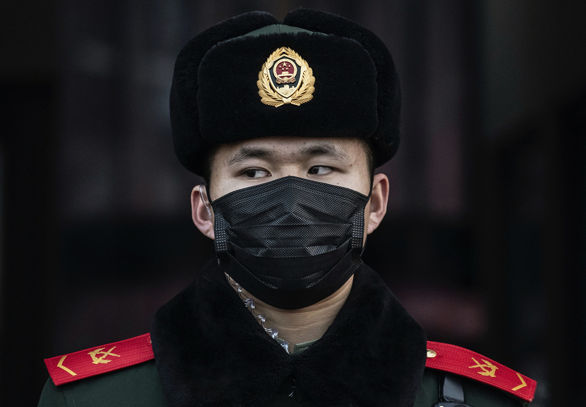 1月22日,北京火車站一名警察帶著面罩。(Photo by Kevin Frayer/Getty Images)