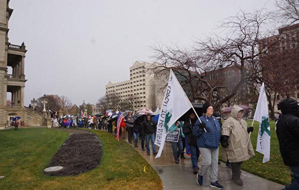 密歇根州的集會於2020年12月12日中午12時開始,12時30分左右開始耶利哥遊行。上千名來自密歇根州各界民眾冒雨圍繞密歇根州國會大廈的整個街區遊行七次,祈禱腐敗和選舉舞弊的城牆倒塌。(林慧心/大紀元)  密歇根
