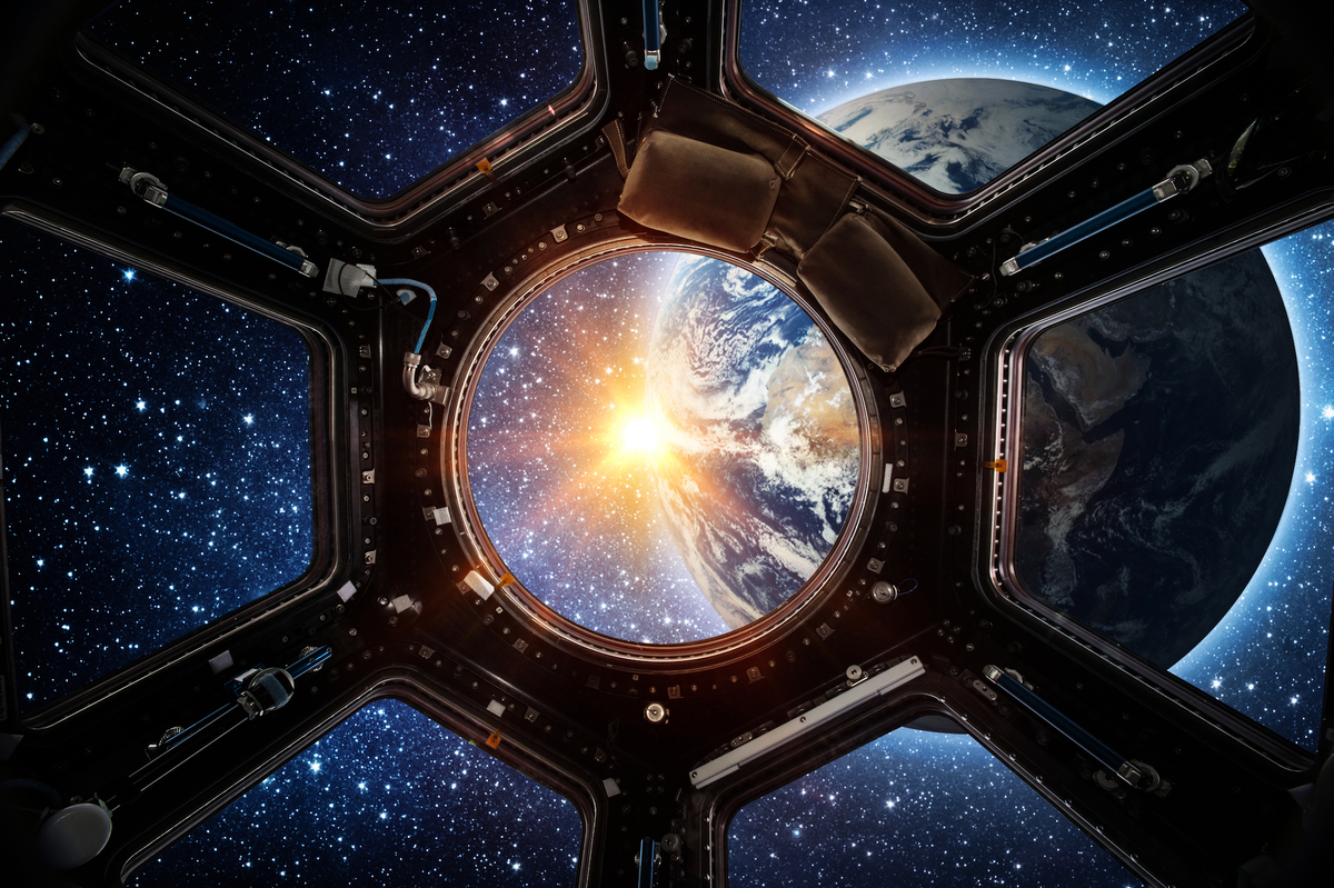 從國際太空站內部看到的地球和升起的太陽。(ShutterStock)