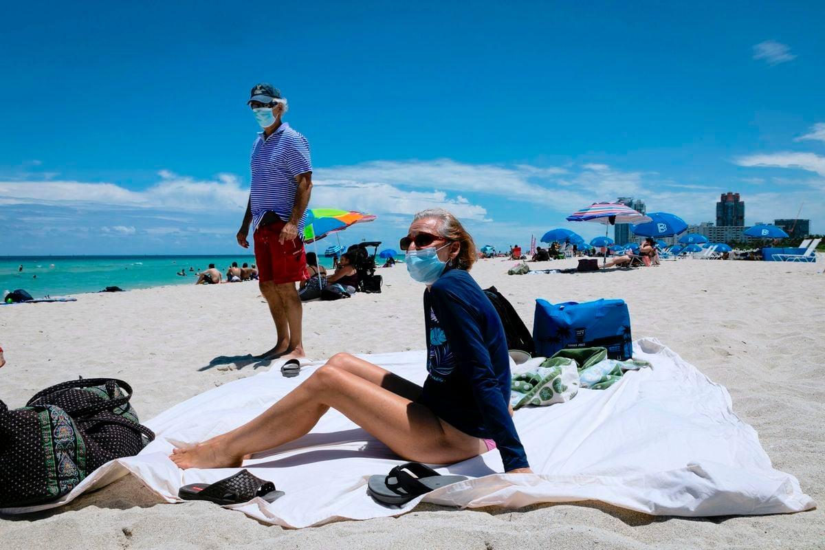 圖為2020年6月16日,美國民眾戴著口罩在佛羅里達州邁阿密海灘上曬太陽。(Eva MARIE UZCATEGUI/AFP/Getty Images)