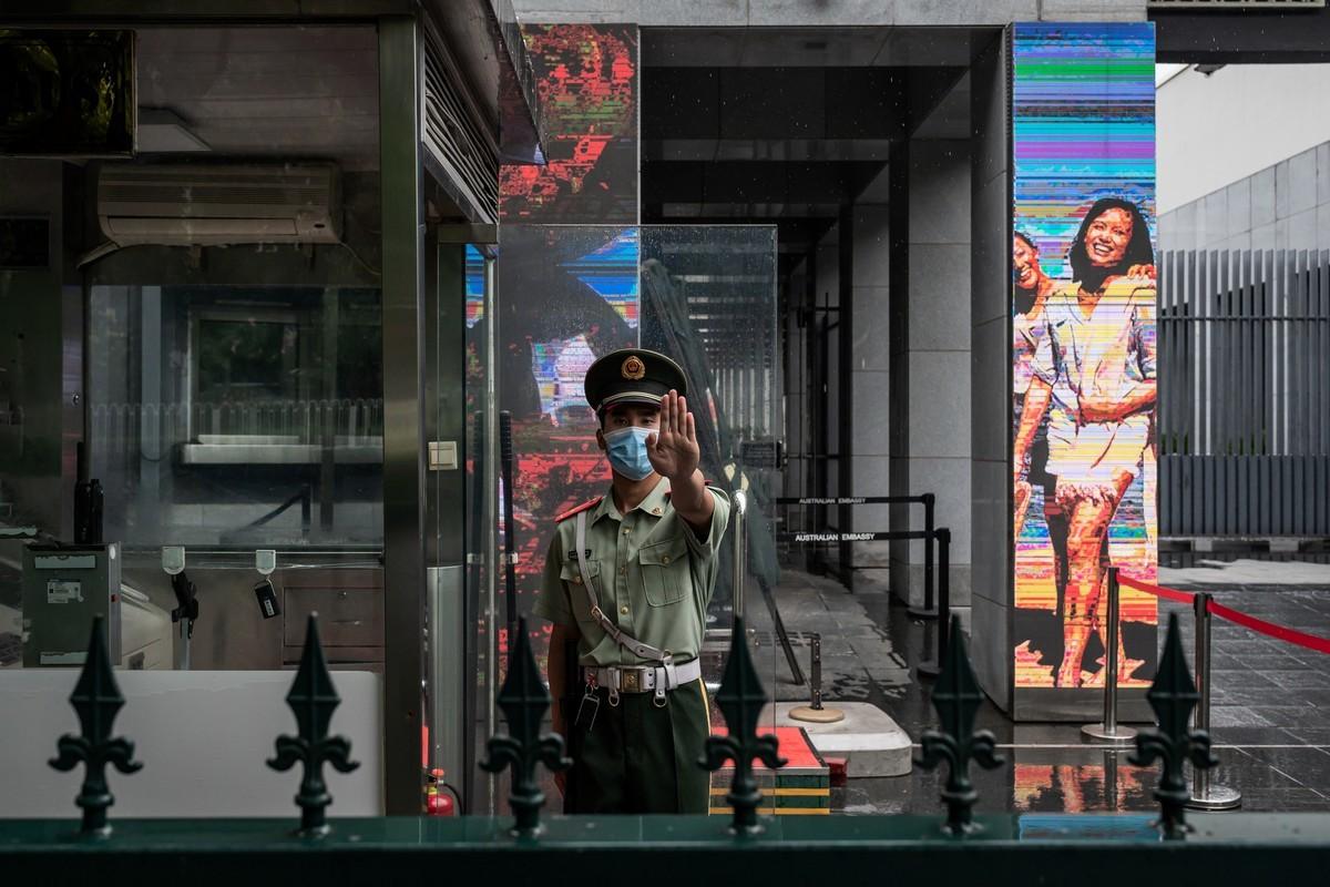 《澳洲金融評論報》記者史密斯(Michael Smith)自述了逃離中國的內幕。圖為一名中共哨兵於2020年7月9日站在澳洲駐北京大使館的入口處、做出禁止入內的手勢。(NICOLAS ASFOURI/AFP)