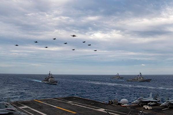 2月9日,美軍雙航母在南海演練,艦載機編隊飛躍艦隊上空。(美國海軍)