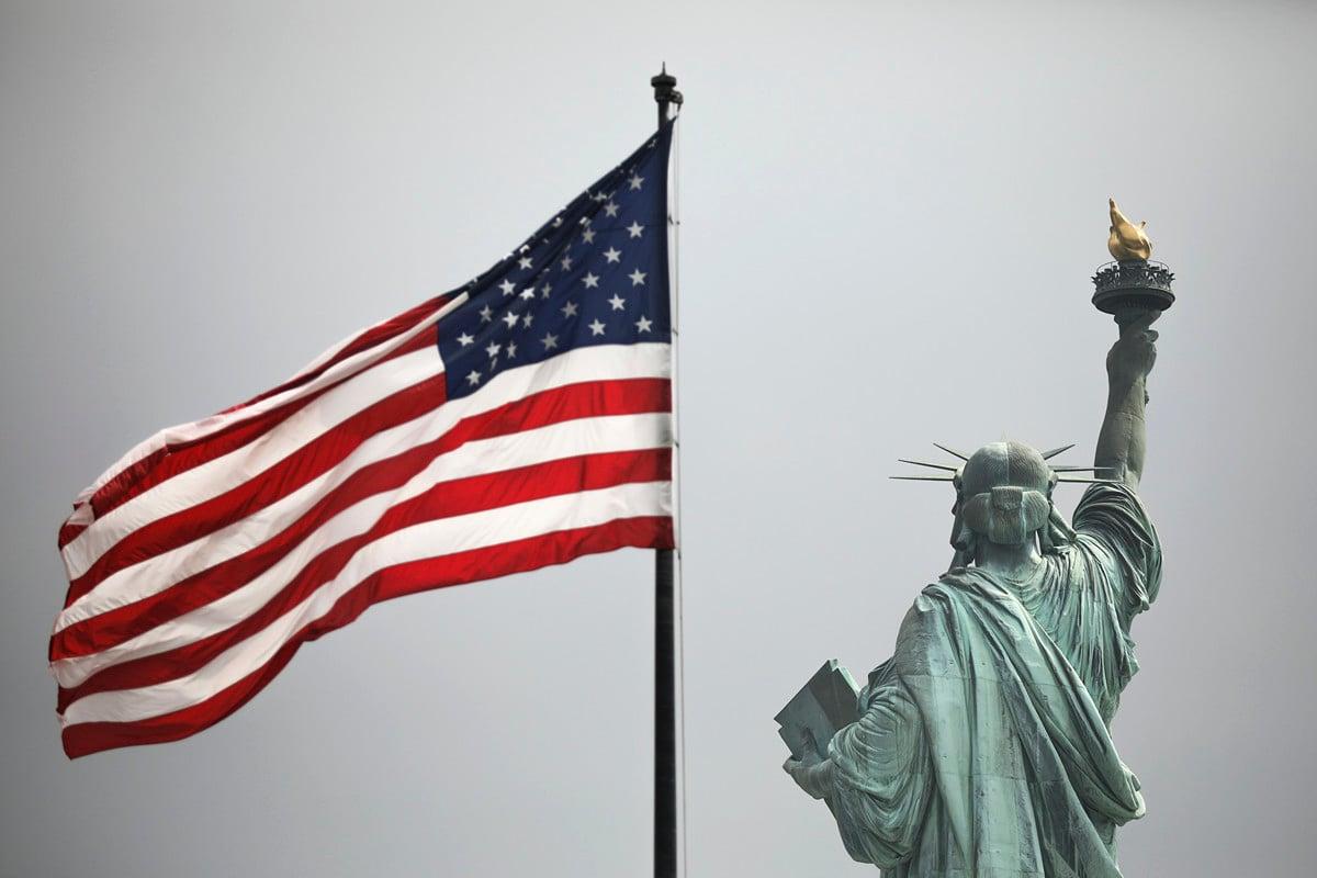 香港作家及傳媒工作者陶傑透露,在《香港人權與民主法案》生效後,有個親共富商搭乘私人飛機前往美國時,被拒絕入境。圖為2019年8月14日,象徵美國的紐約自由女神像和美國國旗。(Drew Angerer/Getty Images)