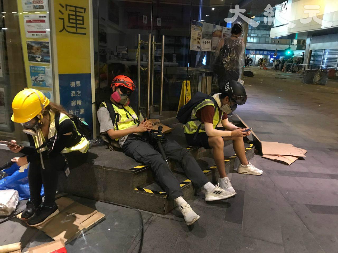 媒體記者為記錄反送中事件,累了就在路邊休息。(余鋼/大紀元)