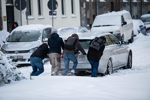 2021年2月8日,德國哈勒(Halle),四位民眾合力在雪中推著一輛汽車。(Jens Schlueter/Getty Images)