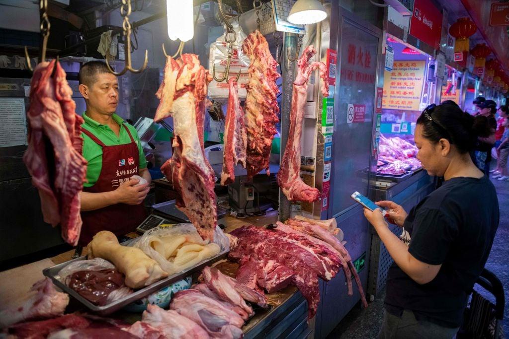 中國國內豬肉價格飆漲高達50%,肉類進口應聲增加,造成全球供應緊張,並在各國肉類市場中引發連鎖反應。圖為中國民眾購買豬肉。(NICOLAS ASFOURI/AFP/Getty Images)