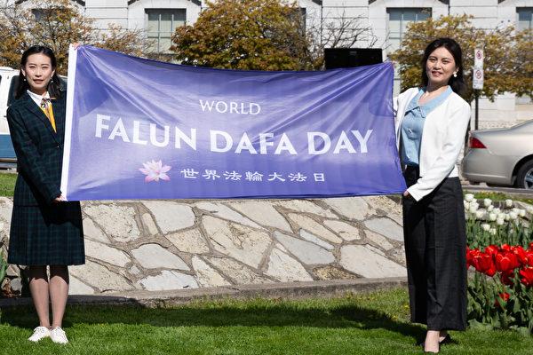 5月13日,多倫多青年法輪功學員嚴妮娜(右)和李思儀(左)參加金斯頓市法輪大法日昇旗儀式。(文森特⋅杜提供)