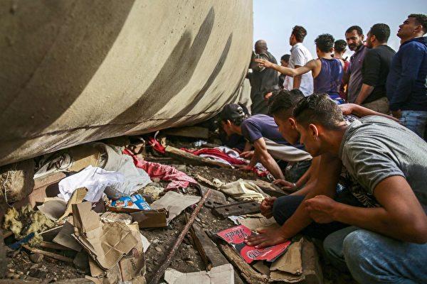 列車翻覆後,人們在檢查車廂地下。(AYMAN AREF/AFP via Getty Images)