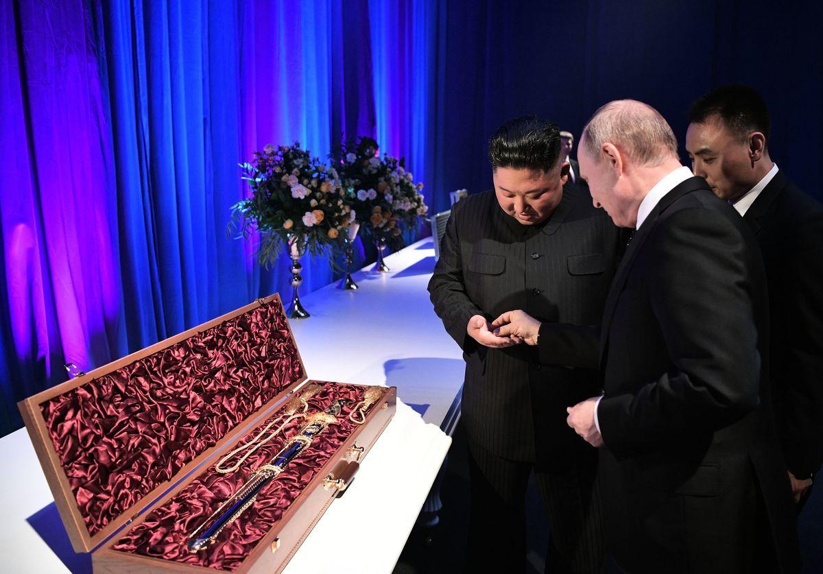 2019年4月25日,在俄羅斯遠東海參崴港,俄羅斯總統普京和北韓領導人金正恩在遠東聯邦大學舉行會晤後交換禮物。普京向金正恩手裏塞了一個硬幣。(ALEXEY NIKOLSKY/AFP/Getty Images)