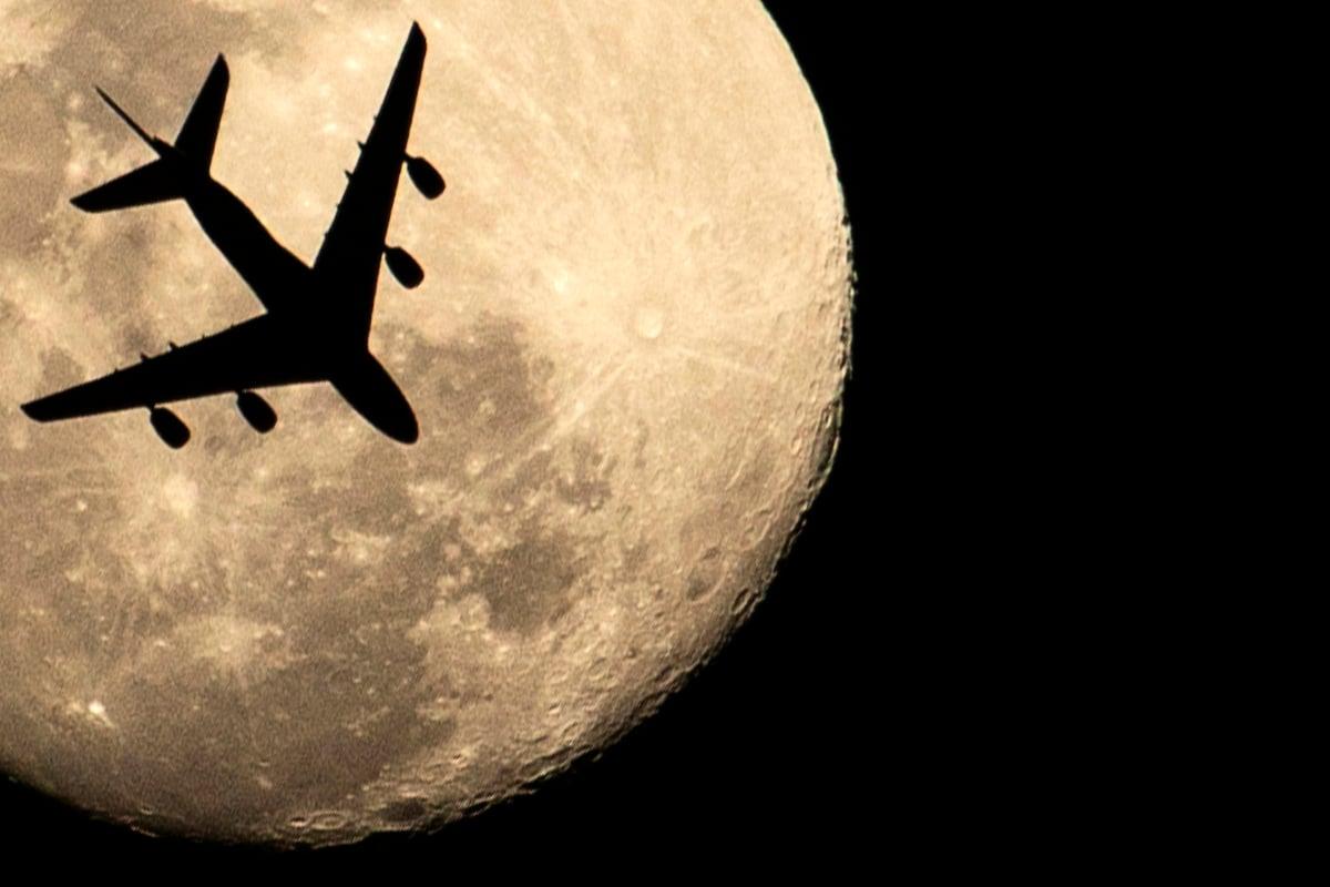 圖為一架飛機在夜空中劃過。(HUSSEIN FALEH/AFP via Getty Images)