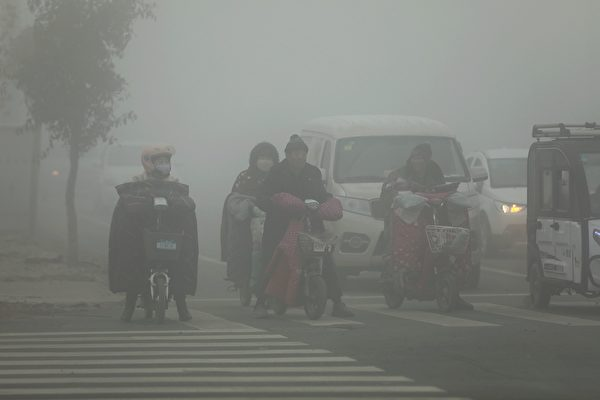 大陸多地遭新年首輪「霾伏」,69個市啟動重污染預警。圖為去年12月7日,人們在陰霾籠罩的山東菏澤曹縣街頭騎行。(大紀元資料室)