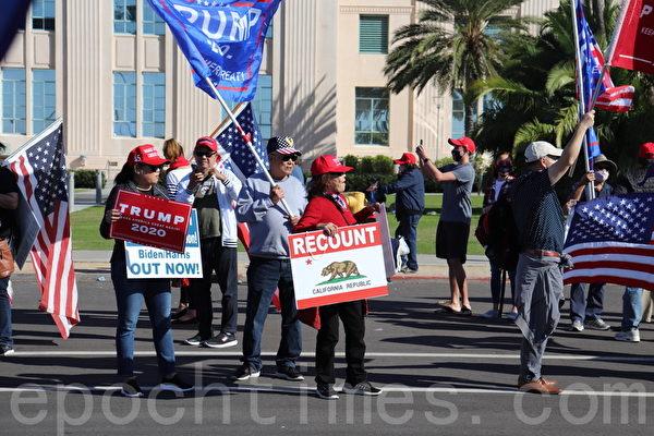 11月14日,聖地牙哥縣選民響應全國挺特朗普集會,在聖地牙哥縣政府大樓前的車道旁聲援特朗普。圖為抗議者手持寫有「重計選票」和「特朗普2020」的標語(鄧舒語/大紀元)
