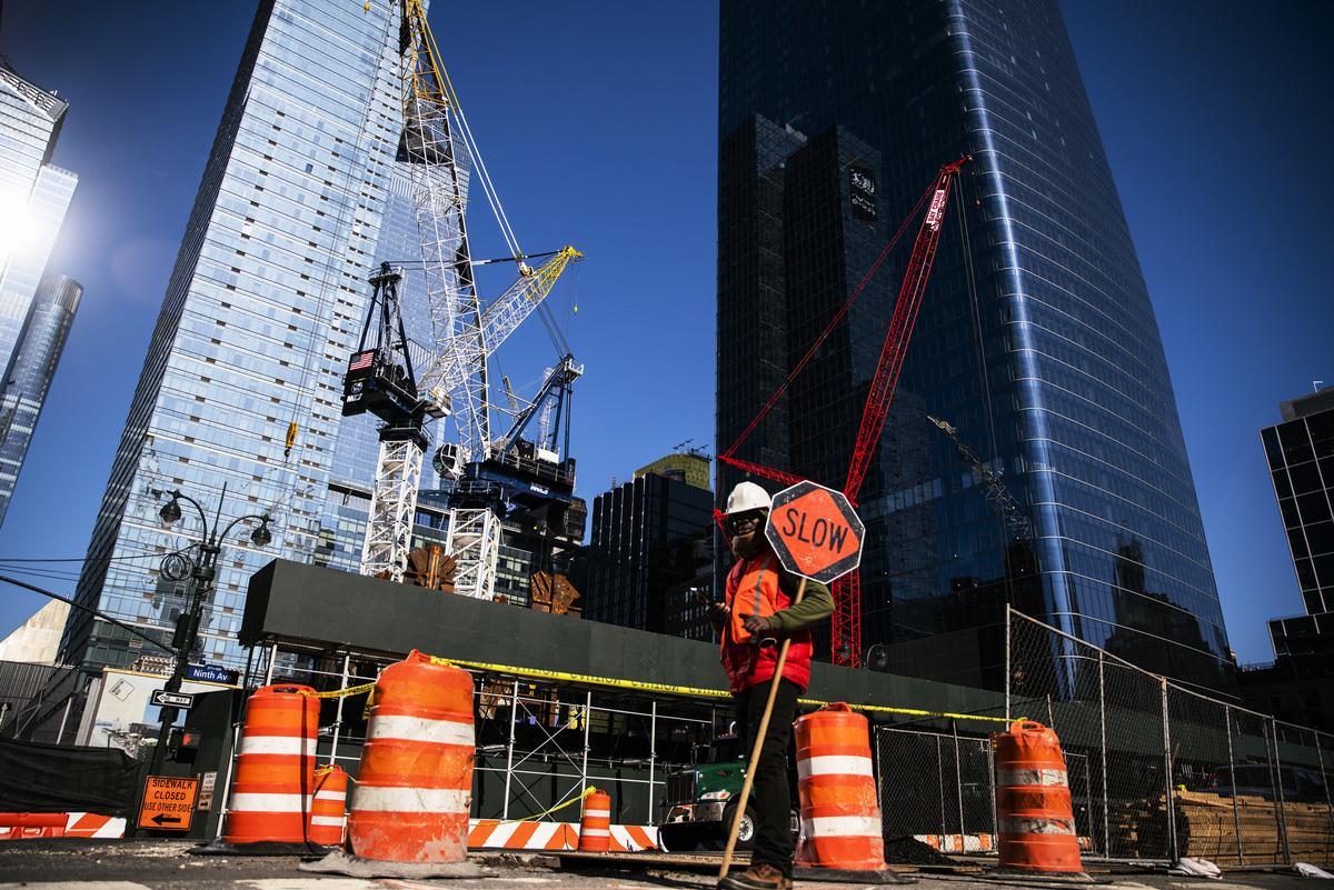 美國失業率數據顯示,特朗普總統在2016年贏得的州,在這次疫情中的經濟表現較好。圖為2020年3月26日,紐約市一名建築工人在大樓工地前指引交通。(Eduardo Munoz Alvarez/Getty Images)