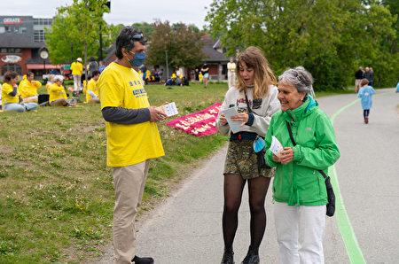 2021年5月30日星期日,加拿大魁北克部份法輪功學員在舍布魯克市(Sherbrooke)舉行遊行活動,慶祝世界法輪大法日暨法輪大法(法輪功)洪傳世界29周年。圖為活動中法輪功學員向民眾傳遞法輪功真相資料。(大紀元)
