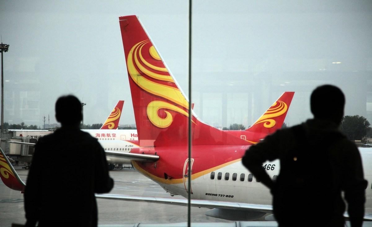 圖為2014年6月12日海口機場的旅客在觀望海航公司的飛機。(AFP/Getty Images)