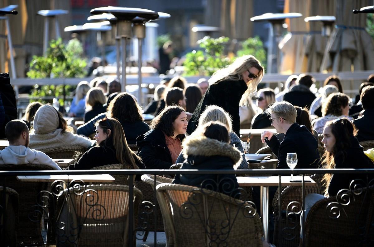 2020年3月26日,中共病毒在瑞典肆虐,人們在斯德哥爾摩中心一個廣場的露台上享受陽光。(JANERIK HENRIKSSON/TT News Agency/AFP via Getty Images)