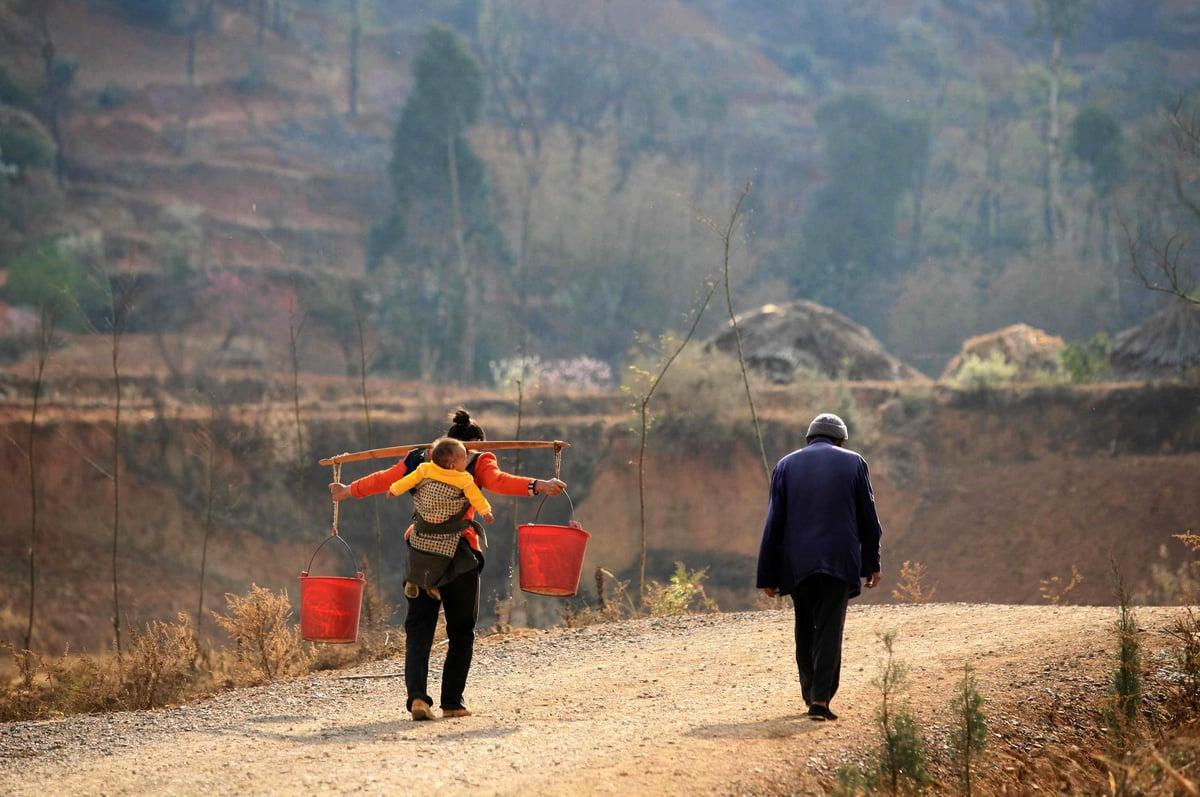 圖為2012年2月雲南省發生乾旱,宜良縣的一名女子用扁擔將井水挑回家中。(AFP/Getty Images)