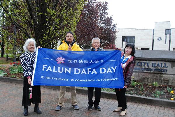 5月7日上午11點,一面藍底白字、印有中英文「世界法輪大法日」旗,在著名的尼亞加拉瀑布市市政廳前升起。法輪大法學員合照留念。(伊鈴/大紀元)