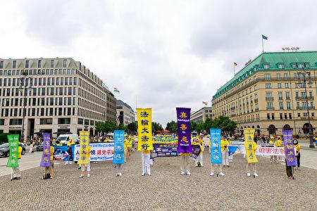 2021年7月17日,來自德國、瑞士和奧地利的部份法輪功學員在柏林勃蘭登堡門舉行集會,紀念7·20反迫害22周年。(張清颻/大紀元)