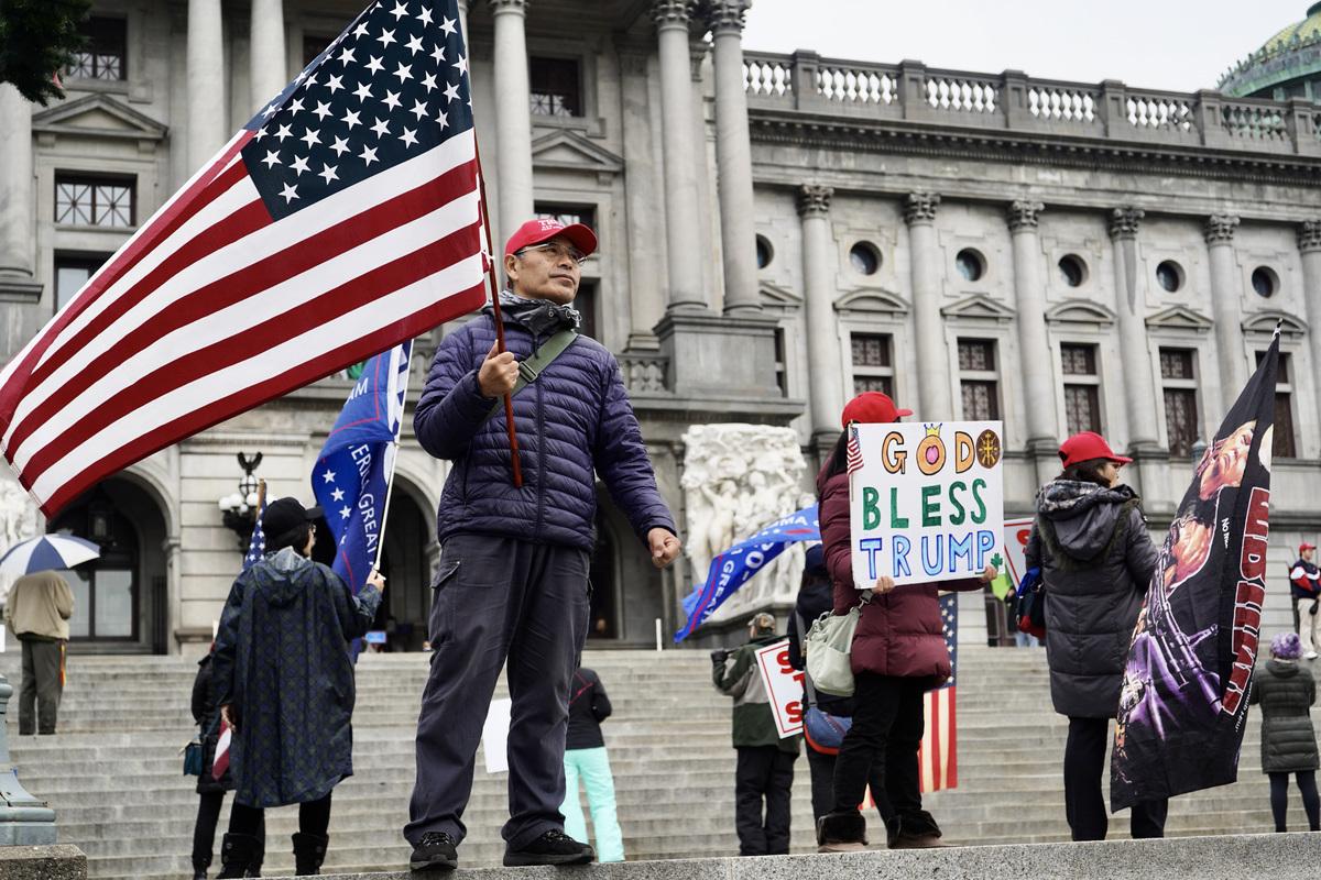 2020年11月30日,賓州議會大廈外的抗議者高舉「神祐特朗普」的標語牌和美國國旗。(李臻婷/大紀元)
